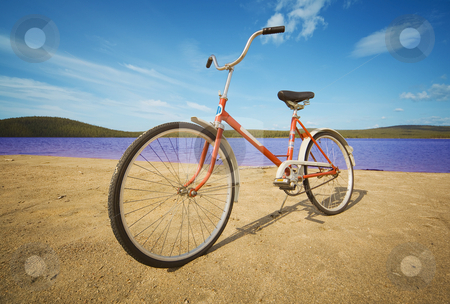 Old-fashioned bicycle on summer beach stock photo, Old-fashioned bicycle on a summer beach against sand, water and hills by Alexey Romanov