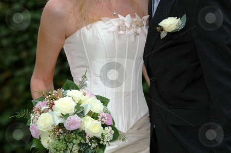 Wedding stock photo, Wedding couple standing together holding flowers. by Lars Christensen