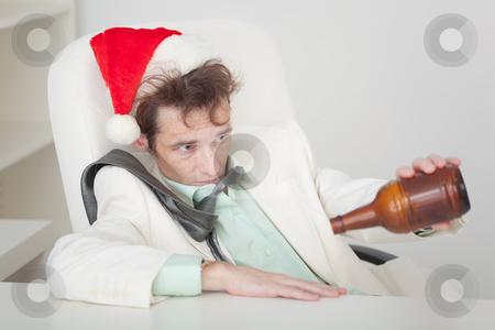 Drunken person in Christmas cap with bottle in a hand stock photo, The drunken person in a Christmas cap with a bottle in a hand by Alexey Romanov