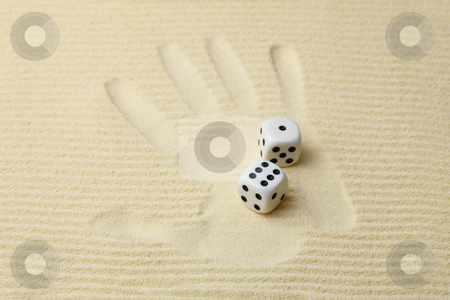 Print of a palm with dices lying on it stock photo, Print of a palm on sand with dices by Alexey Romanov