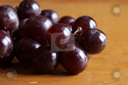 Dark Red Grape Cluster stock photo, A cluster of juicy red grapes on a wood table.  by Chris Hill
