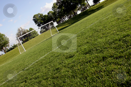 Sunlit Soccer Net stock photo, A view of a net on a vacant soccer pitch.  by Chris Hill