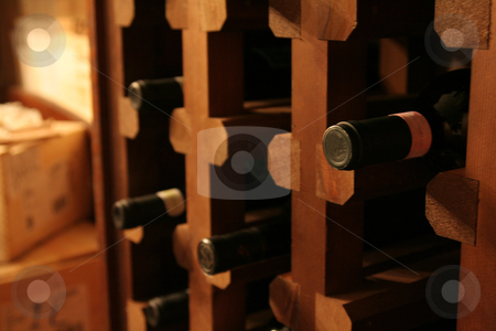 Wine Bottle Rack stock photo, A bunch of wine bottles in a rack in a wine cellar.  by Chris Hill