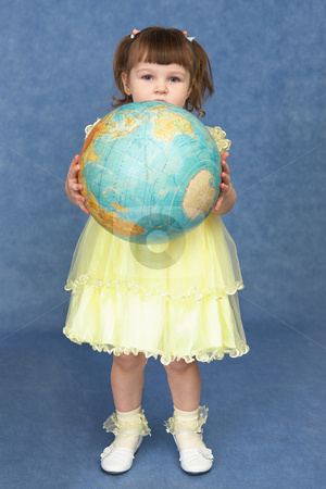 Little girl holding a large globe stock photo, Little girl holding a large globe on a blue background by Alexey Romanov