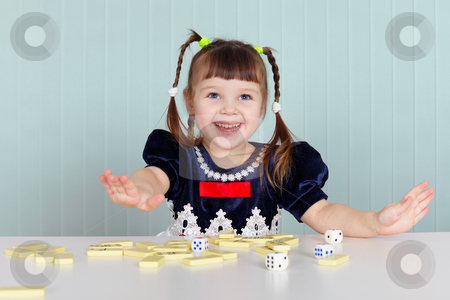 Happy beautiful child plays with toys on table stock photo, The happy beautiful child plays with toys on the table by Alexey Romanov