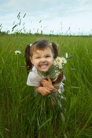 Cheerful child embraces wild flowers stock photo, The cheerful child embraces wild flowers in the field by Alexey Romanov