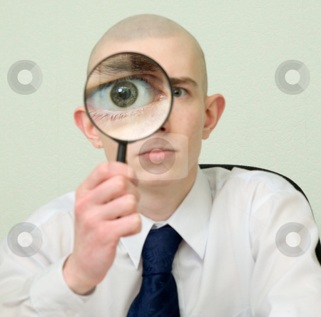Guy looks through the big magnifier stock photo, The guy looks through the big magnifier by Alexey Romanov