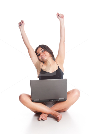 Online Success stock photo, Attractive female having online sucess, sitting cross-legged with a laptop, and her hands/arms up in the air. by ChristopherStephenson