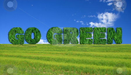 Go Green sign over fresh grass  stock photo, Textured go green sign over fresh grass and lue sky background.