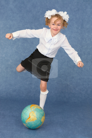 Schoolgirl kicks globe as footballer stock photo, Schoolgirl kicks the globe as a footballer by Alexey Romanov
