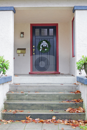 Black door Stucco Home stock photo, Maroon bordered black door of beige stucco house with Christmas wreath by bobkeenan