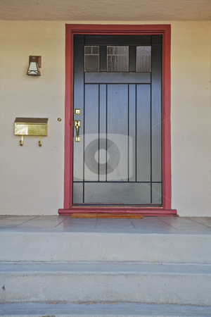 Black door burgundy trim stock photo, Black door with brass fitting with burgundy trim on a beige stucco house by bobkeenan