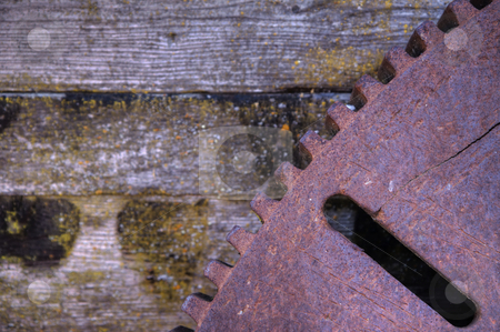 Iron Gear stock photo, Old rusted iron gear against wood background from old foundry by bobkeenan