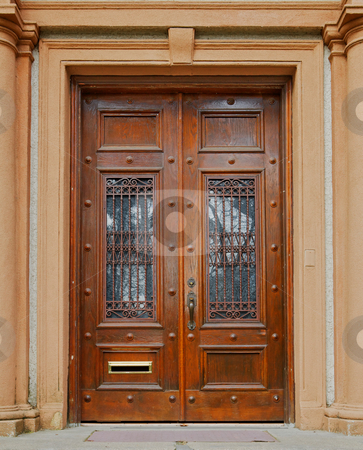 Ornate wood doors stock photo, Ornate stained wood doors with wrought iron grating over glass windows by bobkeenan