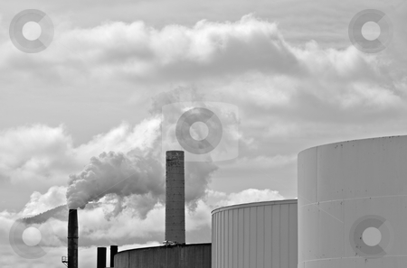 Smoke stacks fuel tanks BW stock photo, Black and white image of four smoke stacks with one billowing steam with three fuel tanks by bobkeenan