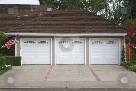 Three car garage flag stock photo, Beige three ar garage with white doors and brick and red brick driveway by bobkeenan