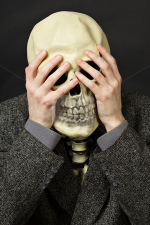 Skeleton covering his eyes stock photo, Skeleton covering his eyes on a dark background by Alexey Romanov