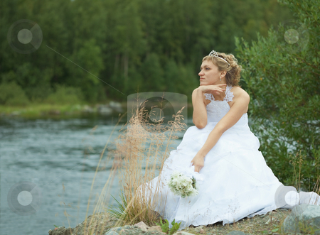 Sad bride sits on river bank stock photo, The sad bride sits on river bank and looks afar by Alexey Romanov
