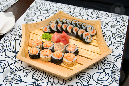 Sushi on wood plate stock photo, At restaurant: Set of sushi on wood plate. by olinchuk