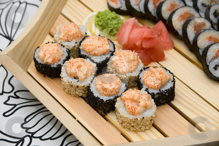 At sushi bar stock photo, At restaurant: Set of sushi on wood plate. by olinchuk