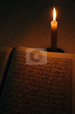 Holly quran stock photo, holly quran with single candle light in dark room by Bayu Harsa