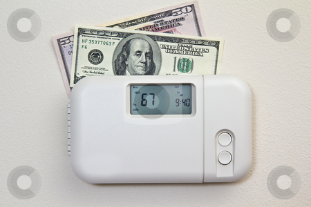 Home Heating Costs stock photo, In door heating thermostat set at a room temperature and money by tab62