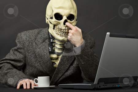 The skeleton picks in a nose stock photo, The skeleton picks in a nose on table with laptop by Alexey Romanov
