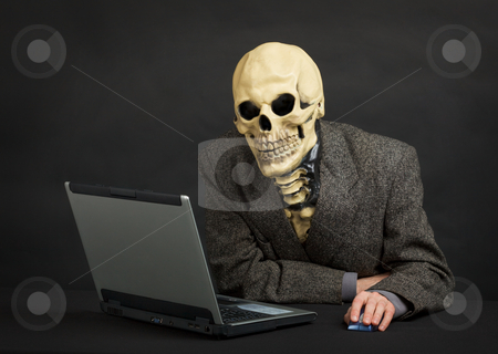 Terrible skeleton sits at black office with laptop stock photo, The terrible skeleton in a suit sits at black office with the laptop by Alexey Romanov