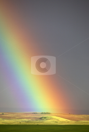 Colorful rainbow touching down on a Saskatchewan hill stock photo, Colorful rainbow touching down on a Saskatchewan hill by Mark Duffy