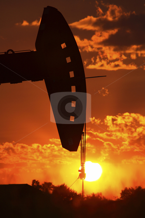 Oil rig pump jack silhouetted by setting sun stock photo, Oil rig pump jack silhouetted by setting sun by Mark Duffy