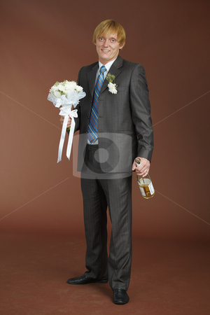 Groom with bouquet and bottle of sparkling wine stock photo, A young groom with a bouquet and a bottle of sparkling wine by Alexey Romanov