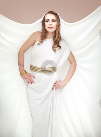 Portrait of young woman in greek inspired white dress, smiling stock photo, a studio portrait of a beautiful young woman, wearing a long, white, ancient greek inspired dress, with a piece of material on her head, posing with her hands on her hips. by dan comaniciu