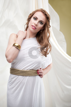 Portrait of young woman in greek inspired white dress, smiling stock photo, a studio portrait of a beautiful young woman, wearing a long, white, ancient greek inspired dress, surrounded by a flowy, wavy white fabric. by dan comaniciu
