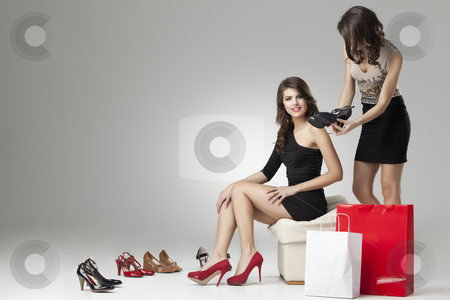 Two glamorous women trying high heels  stock photo, two glamorous women shopping high heels by dan comaniciu