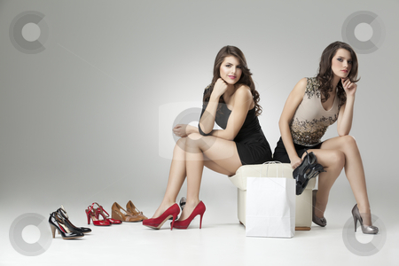 Two glamorous women trying high heels  stock photo, two glamorous women red gray high heels by dan comaniciu
