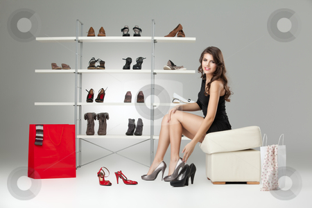 Young woman sitting trying shoes looking happy stock photo, young woman black dress shoes stand high heels by dan comaniciu
