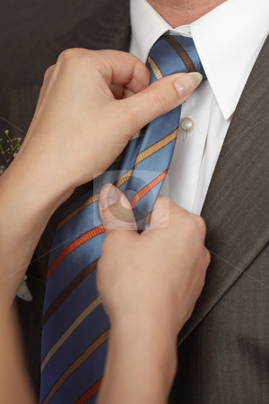 Woman ties man to tie stock photo, A woman ties a man to tie - close-up by Alexey Romanov