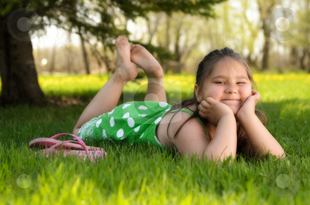 Kid Relaxing Outside stock photo, A young girl laying in the grass relaxing and enjoying the spring weather. by Richard Nelson