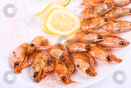 Shrimps stock photo, roasted shrimps with lemon closeup isolated on a white background by olinchuk