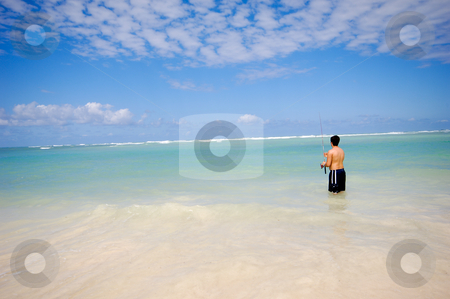 Fishing on beach stock photo, Man is fishing on An exotic beach with white sand, the sky is blue with clouds. Dominican Republic, Punta Cana. by Lars Christensen