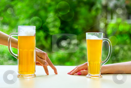 Beer romantic stock photo, two hands, man and woman with beer in glass by olinchuk
