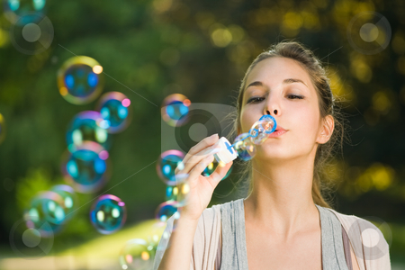 As easy as blowing bubbles. stock photo, As easy as blowing bubbbles, beautiful young brunette making soap bubbles outdoors. by exvivo