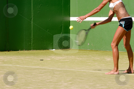 Womman is palying tennis stock photo, Woman is serving the ball. Note that hand, ball and racket is in motion blur. by Lars Christensen