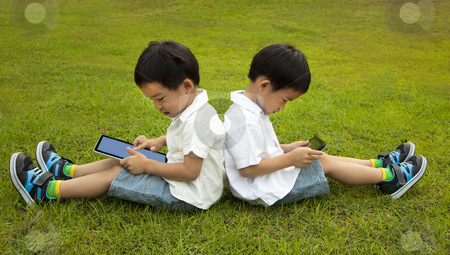 Two kids using touchscreen tablet PC on the grass  stock photo, Two kids using touchscreen tablet PC on the grass  by tomwang