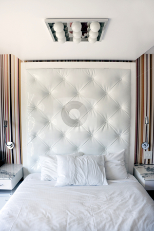 White Hotel Bedroom stock photo, A modern white hotel bedroom with night stand by Kevin Tietz