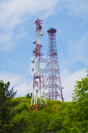 Cell phone towers and antennaes stock photo, Cell phone tower against blue sky with scattered clouds by Christian Delbert