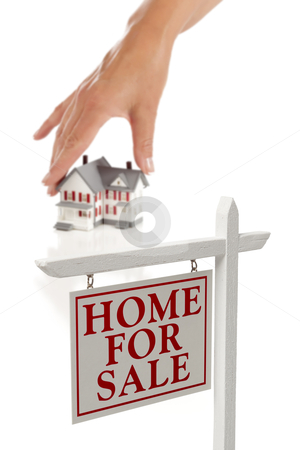Womans Hand Choosing Home with Real Estate Sign in Front stock photo, Womans Hand Choosing House with Home For Sale Real Estate Sign in Front Isolated on White. by Andy Dean