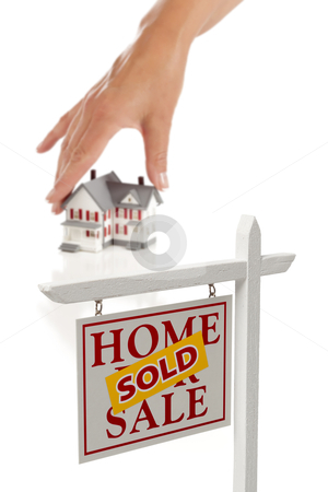 Womans Hand Choosing Home with Sold Real Estate Sign stock photo, Womans Hand Choosing Home with Sold Home For Sale Real Estate Sign in Front Isolated on White. by Andy Dean