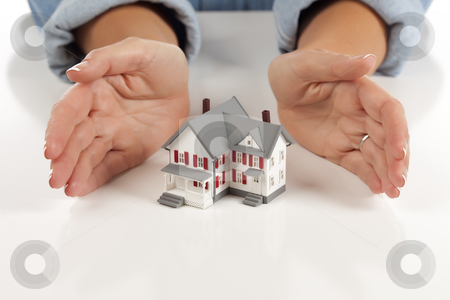 Womans Hands Around Model House stock photo, Womans Hands Around Model House on White Surface. by Andy Dean