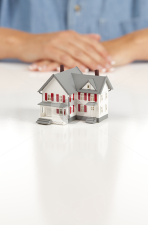 Womans Folded Hands Behind Model House stock photo, Womans Folded Hands Behind Model House on White Surface. by Andy Dean
